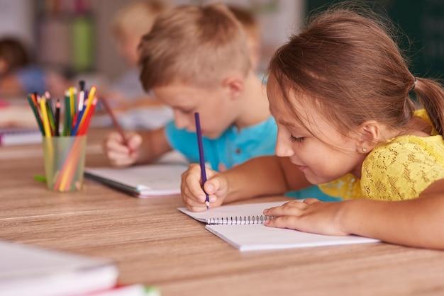 Kleines mädchen, das in ihrem notizbuch zeichnet