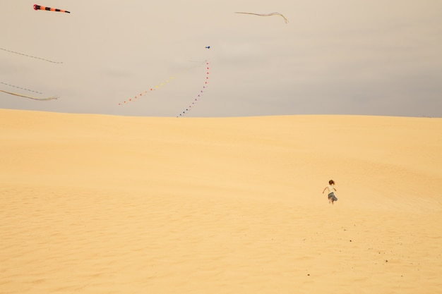Kleines mädchen, das in richtung zu einem bereich läuft, in dem drachen in die sanddünen eines strandes fliegen