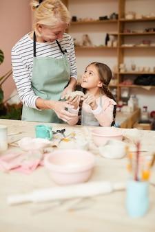 Kleines mädchen, das keramik genießt