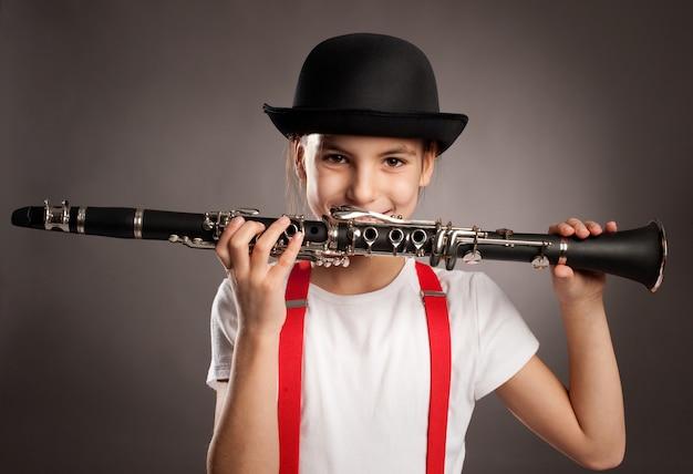 Kleines mädchen, das klarinette auf einem grauen hintergrund spielt