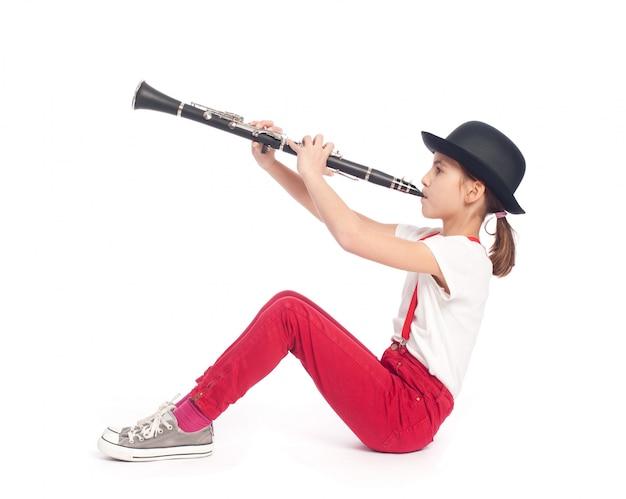 Kleines mädchen, das klarinette auf einem weißen hintergrund spielt
