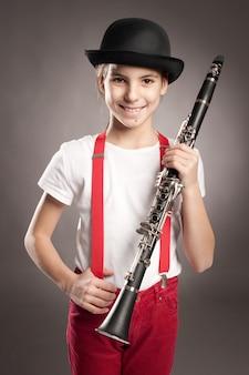 Kleines mädchen, das klarinette auf grau spielt