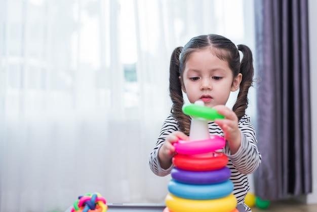 Kleines mädchen, das kleines spielzeugband im haus spielt. bildung und glück lifestyle-konzept