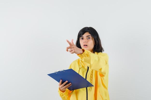Kleines mädchen, das klemmbrett hält, anweisungen im gelben kapuzenpulli gibt und fokussierte vorderansicht schaut.