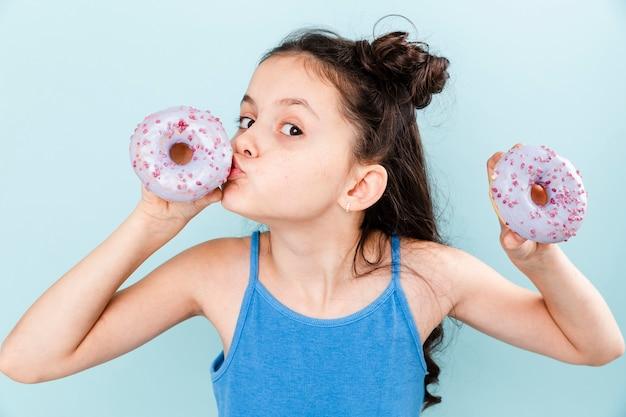 Kleines mädchen, das köstlichen donut küsst