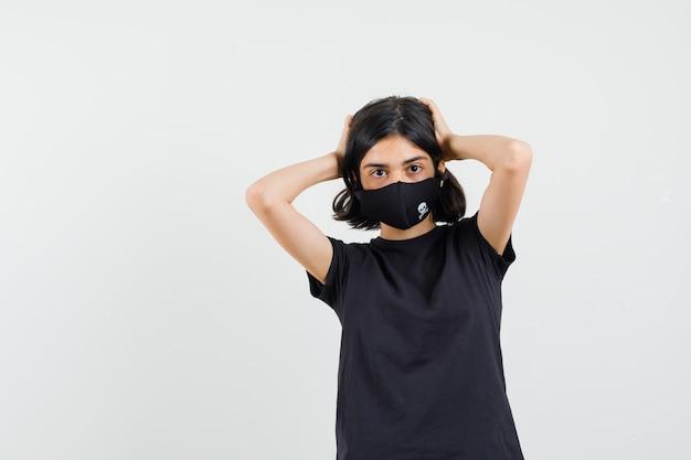 Kleines mädchen, das kopf mit händen im schwarzen t-shirt, maske, vorderansicht umklammert.
