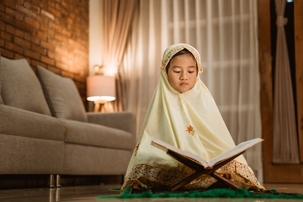 Kleines mädchen, das koran liest, der muslimischen hijab trägt