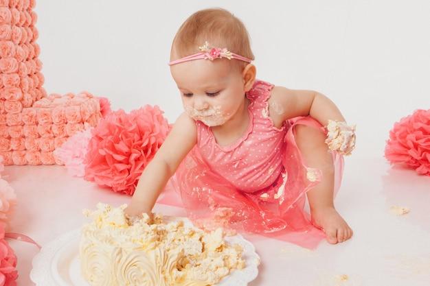 Kleines mädchen, das kuchen mit ihren händen auf weiß isst. das kind ist mit essen bedeckt. die süße ruiniert. geburtstag, feiertage, kochen