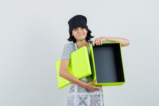 Kleines mädchen, das leere geschenkbox hält und im küchenkleid lächelt,