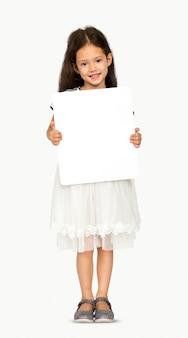 Kleines mädchen, das leeres kopien-raum-papierbrett-studio-porträt hält