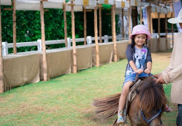 Kleines mädchen, das lernt, pferd zu reiten