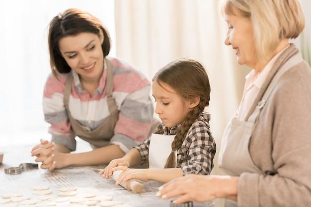 Kleines mädchen, das lernt, teig zu rollen und hausgemachtes gebäck oder kekse mit ihrer mutter und großmutter zu machen