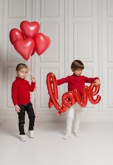 Kleines mädchen, das liebesballon und jungen mit roten ballonherzen auf weißem hintergrund mit raum für text hält