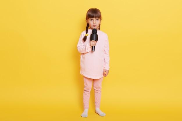Kleines mädchen, das lied mit kamera und ernstem gesichtsausdruck singt, schaut kamera mit besorgtem blick an, verwirrt, um leistung zu arrangieren, lässige kleidung tragend, lokalisiert über gelbem hintergrund.