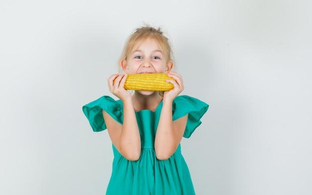 Kleines mädchen, das mais im grünen kleid isst und fröhlich schaut