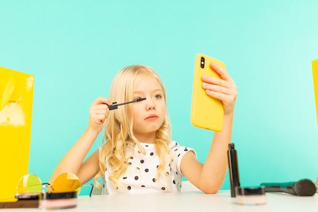 Kleines mädchen, das make-up vor der kamera für vlog tut. arbeitet als blogger und nimmt ein video-tutorial für das internet auf.