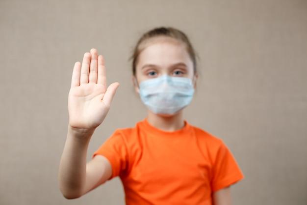 Kleines mädchen, das maske zum schutz trägt. stoppschild anzeigen. stoppen sie das virus und epidemische krankheiten. coronavirus covid-19.stay at home bleiben sie sicher konzept. selektiver fokus auf hand.
