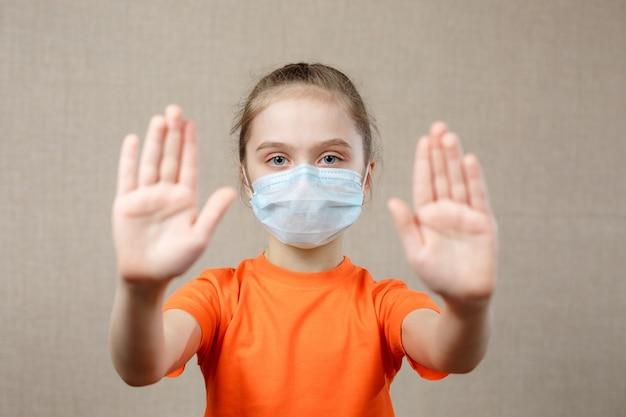 Kleines mädchen, das maske zum schutz trägt. stoppschild anzeigen. stoppen sie das virus und epidemische krankheiten. coronavirus covid-19.stay at home bleiben sie sicher konzept. selektiver fokus.