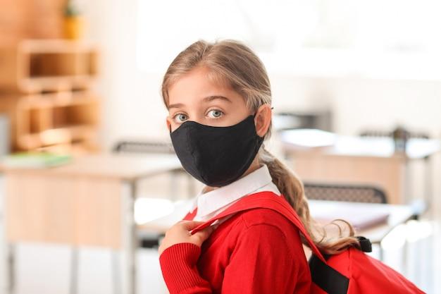 Kleines mädchen, das medizinische maske in der schule trägt