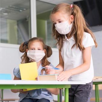 Kleines mädchen, das medizinische masken an der schule trägt