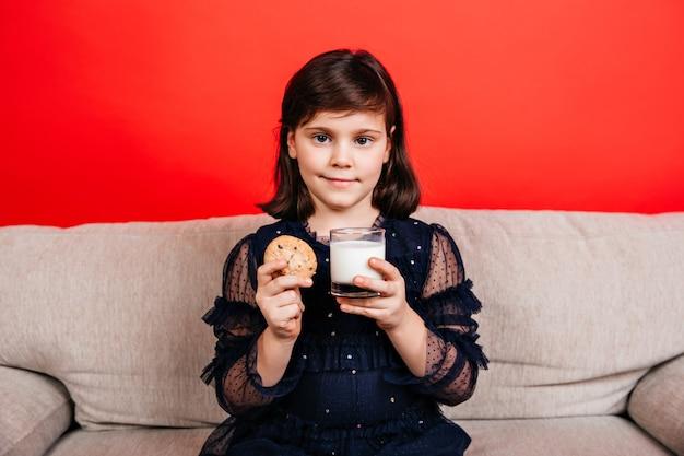 Kleines mädchen, das milch auf roter wand trinkt. innenaufnahme des kindes, das keks isst.