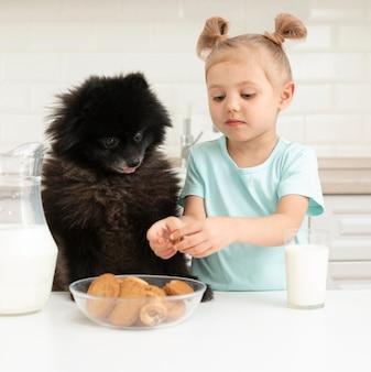 Kleines mädchen, das milch trinkt und mit hund spielt