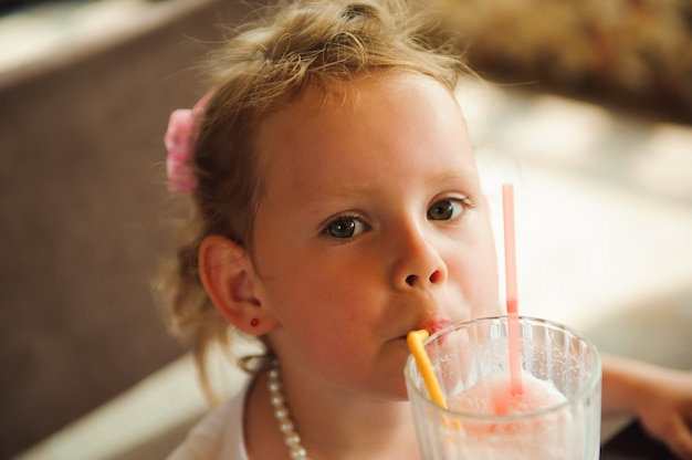 Kleines mädchen, das milchshakes in einem café draußen trinkt.