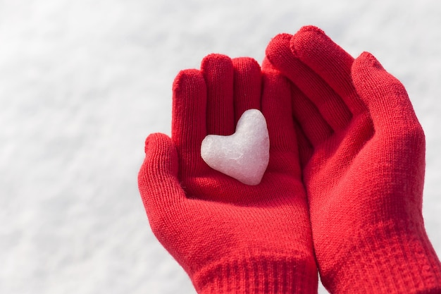 Kleines mädchen, das mini-schneeherz in roten warmen wollhandschuhen hält.