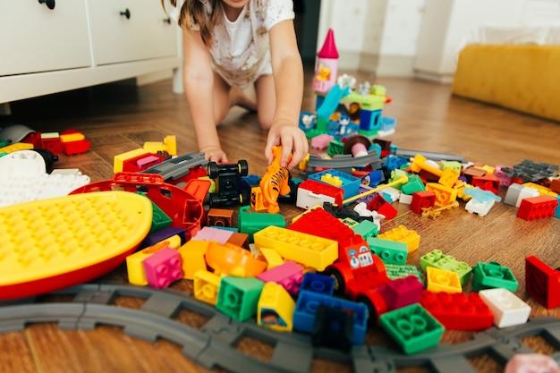 Kleines mädchen, das mit bunten bauklötzen spielt. pädagogisches und kreatives spielzeug und spiele für kleine kinder. spielzeit und chaos im kinderzimmer
