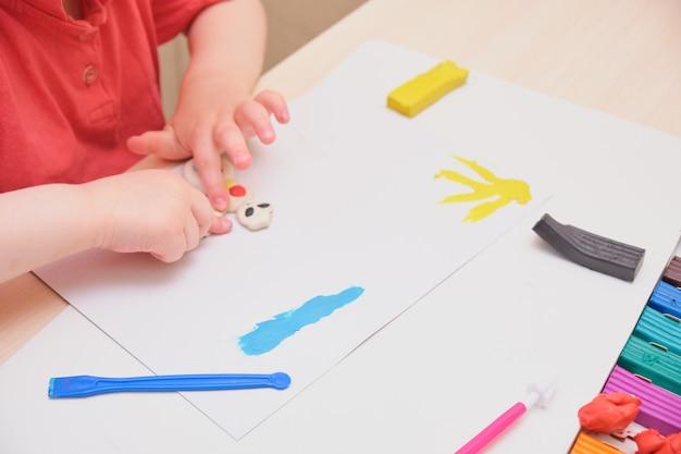 Kleines mädchen, das mit bunter modelliermasse auf dem tisch spielt. home education-spiel mit ton. frühes entwicklungskonzept, das das kind aus plastilin formt