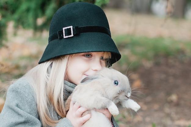 Kleines mädchen, das mit dem grauen kaninchen im freien spielt