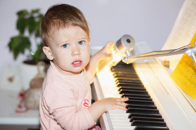 Kleines mädchen, das mit dem klavier spielt