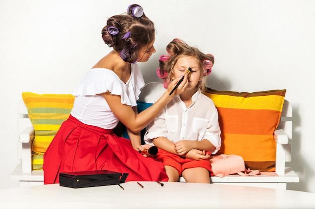 Kleines mädchen, das mit dem make-up ihrer mutter spielt