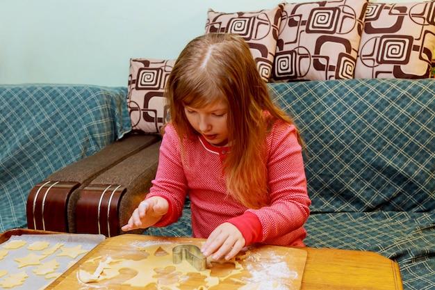 Kleines mädchen, das mit dem vorbereiten des teigs auf dem tisch macht