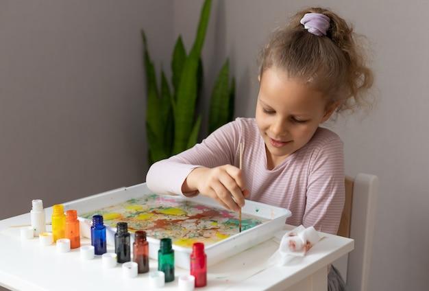 Kleines mädchen, das mit ebru-farben malt und am tisch sitzt