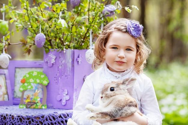 Kleines mädchen, das mit echtem kaninchen im garten spielt. lachendes kind bei ostereiersuche mit haustierhase. frühlingsspaß im freien für kinder mit haustieren
