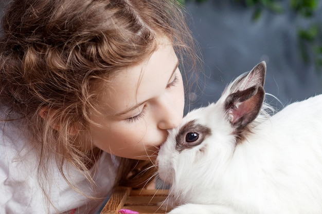 Kleines mädchen, das mit echtem kaninchen spielt. kind und weißer hase an ostern. kind küssen haustier. spaß und freundschaft für tiere und kinder.