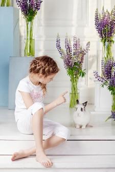 Kleines mädchen, das mit echtem kaninchen spielt. kind und weißer hase an ostern. kinder und haustiere spielen. spaß und freundschaft für tiere und kinder.