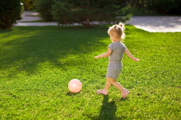 Kleines mädchen, das mit einem ball im park spielt