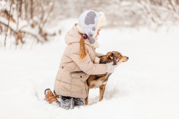 Kleines mädchen, das mit einem hund im winterwald spielt. winterspaß
