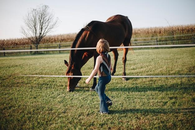 Kleines mädchen, das mit einem pferd spielt