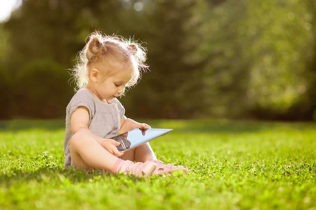 Kleines mädchen, das mit einer tafel im park spielt