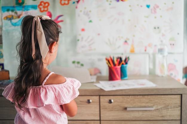 Kleines mädchen, das mit farbstift in papier auf dem tisch im spielzimmer zeichnet, gesundes baby und vorschulkonzept