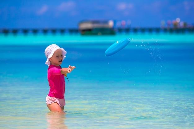 Kleines mädchen, das mit flugscheibe am weißen strand spielt
