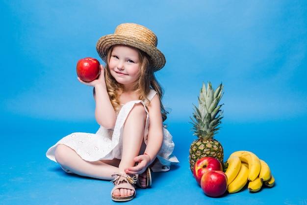 Kleines mädchen, das mit früchten spielt, die auf einer blauen wand lokalisiert werden