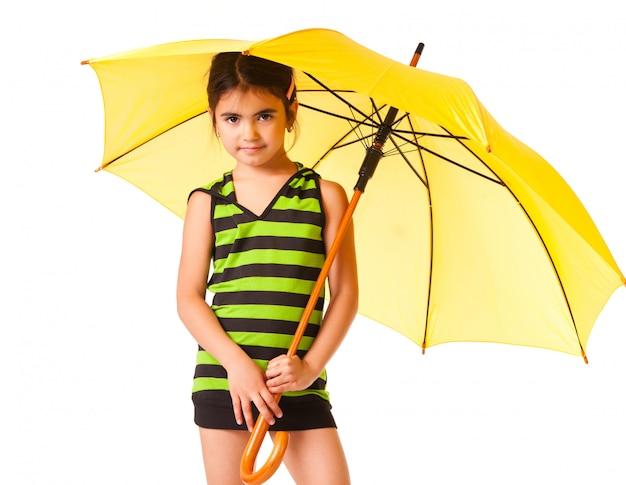 Kleines mädchen, das mit gelbem regenschirm aufwirft