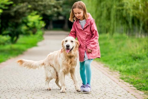 Kleines mädchen, das mit goldenem retriever draußen im park geht