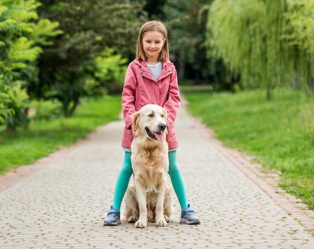 Kleines mädchen, das mit goldenem retrieverhund zwischen füßen auf gepflasterter gasse im park steht