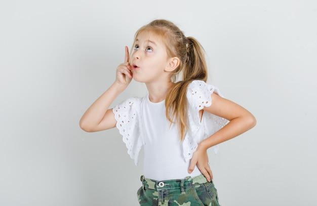 Kleines mädchen, das mit hand auf taille im weißen t-shirt oben zeigt