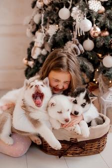 Kleines mädchen, das mit heiseren welpen nahe weihnachtsbaum spielt